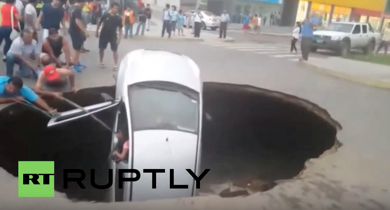 Image: Giant sinkhole swallows car with family still inside in Peru